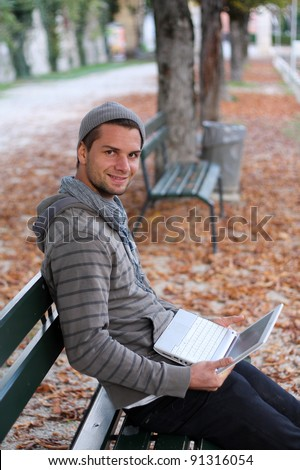 Man sitting on a Bench with notebook smiling