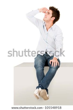 Man sitting on a cube and looking away - isolated over white