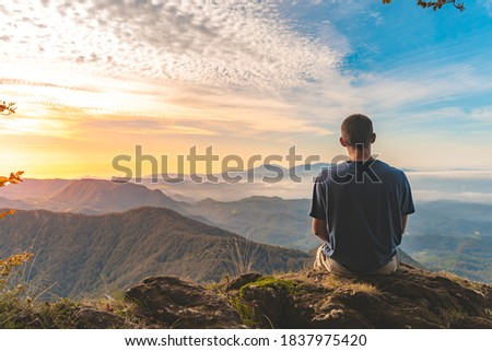 Man sitting on a edge of a cliff and looking at beautiful and rough terrain around him. Adventure solo traveling lifestyle. Wanderlust adventure concept. Active weekend vacations wild nature outdoor.  Photo stock ©