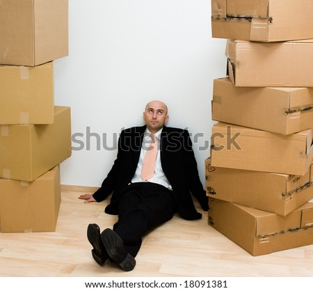 Man sitting on a floor against a wall, with tall stacks of cardboard boxes on each side of him.