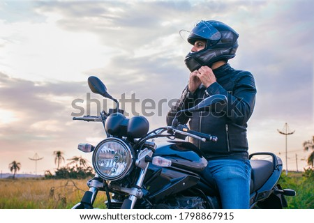 Man sitting on a motorcycle, wearing jeans and a black jacket, fastening his helmet with a landscape in the background. Сток-фото ©