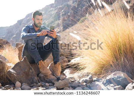 Man sitting on a rock in the mountains texting on a cell phone