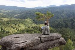 Man sitting on a rock near a lonely pine tree, Altai mountains, Belokurikha city, Russia