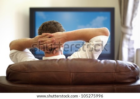 Man sitting on a sofa watching tv with hands folded behind his head - stock photo