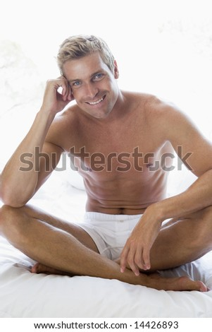 Man sitting on bed smiling