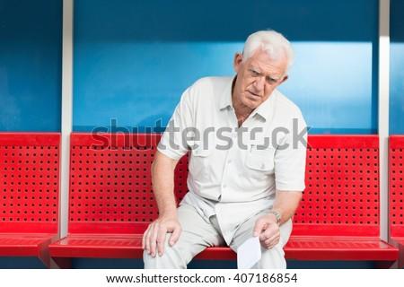 Man sitting on bench at bus stop