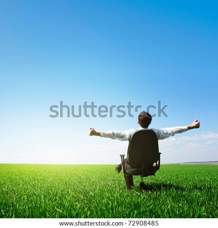 Man sitting on chair on green meadow on blue clear sky background #72908485