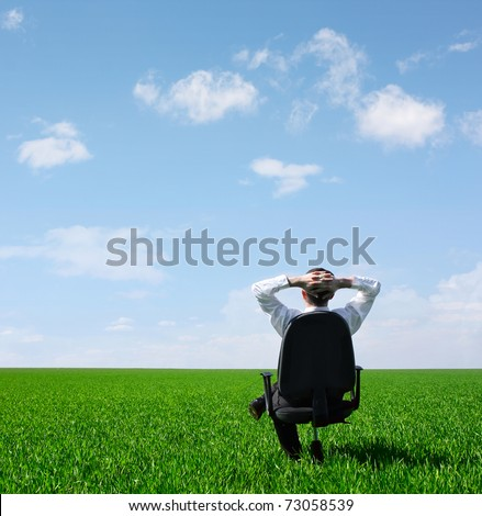 Man sitting on chair on green meadow on blue cloudy sky background