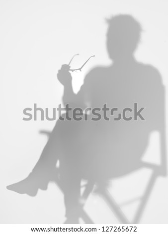 man sitting on director's chair reading a book with eyeglasses in his hand, behind a diffuse surface