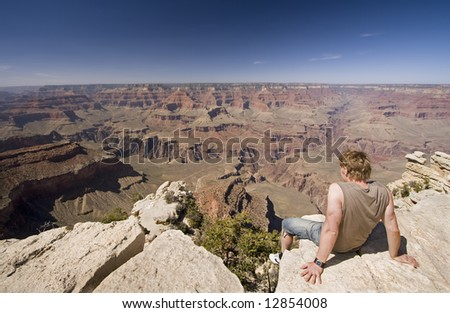 Man sitting on edge of Grand Canyon South rim, Arizona