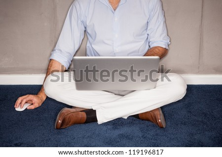 Man sitting on floor with laptop in office - landscape interior.