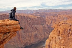 Man sitting on rock formation overlooking Colorado river at horseshoe bend, Arizona. Hiker resting on rock formation high above the valley. Red rocks, man in jacket and panoramic view.