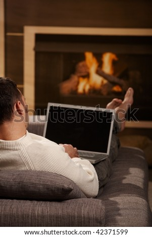 Man sitting on sofa at home in front of fireplace and using laptop computer, rear view.