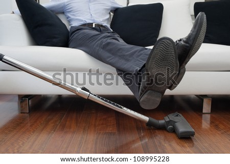man sitting on sofa, feet up to vacuuming