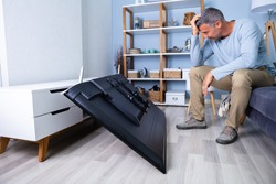 Man Sitting On Sofa In Front Fallen Television With Broken Screen