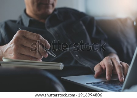 Man sitting on sofa writing on notebook and browsing internet on laptop computer, work from home concept. Male student studying online class via laptop and taking note on notepad, E-learning, close up