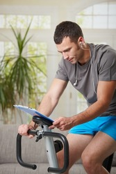 Man sitting on stationary bike at home, looking at training plan.