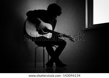Man sitting on stool in dark room playing guitar