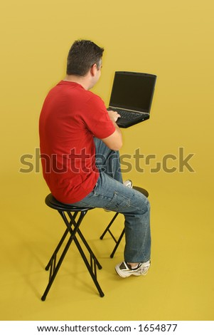 Man sitting on stool with laptop computer.  Back side, full body, over yellow.