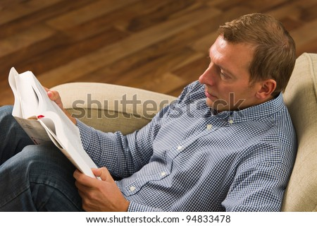 Man sitting on the armchair and reading the book.