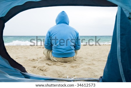 Man sitting on the beach during camping trip.