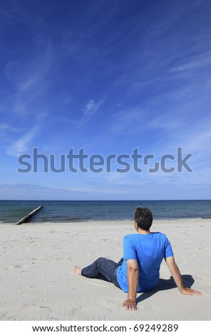 Man sitting on the beach watching the sea