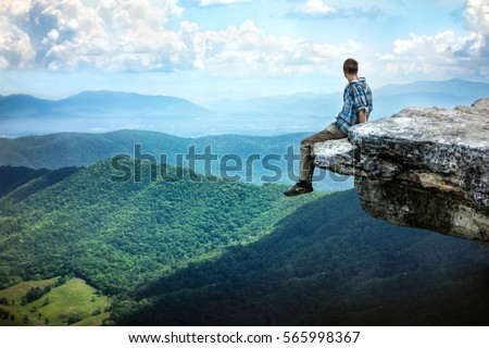 Man sitting on the edge of a cliff contemplating about life.