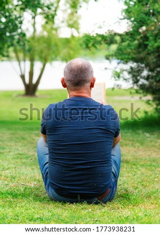Man sitting on the grass and reading a book