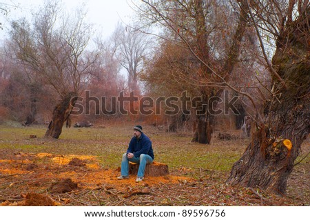 Man sitting on the log worried about uncontrollable cutting of the forests.