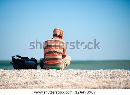 man sitting on the sand by the sea in the sun. Beside him is his backpack with things