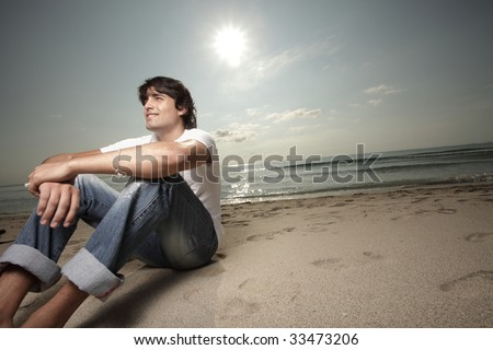 Man sitting on the sand with the sun behind him