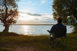 Man sitting on the shore of the lake, at sunset. Silhouette of person oncamping chair against backdrop of the setting sun. Outdoor landscape. Fishing and recreation concept.
