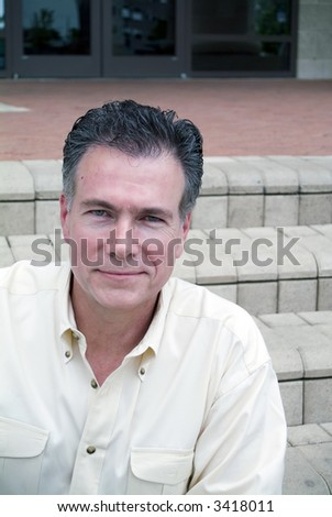 Man sitting on the steps of a building looking happy and friendly.