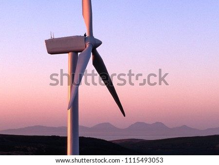 man sitting on top of a wind turbine turned pink by the setting sun; Isle of Jura in the background #1115493053
