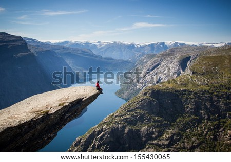 man sitting on trolltunga in...