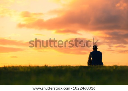 Man sitting watching sunset. Enjoying a peaceful moment, thinking, getting away from it all concept.
