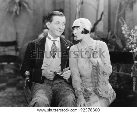Man sitting with a woman who is holding a cigarette