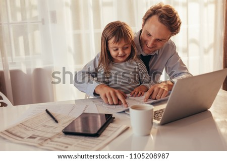 Man sitting with his daughter and looking at a book sitting with laptop computer, tablet and coffee cup on the table. Father spending time with daughter while working at home.