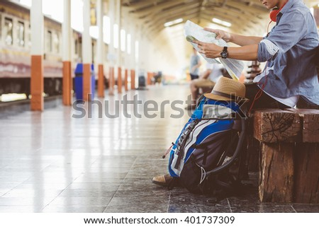 man sitting with map. travel bag at the train station.vintage filter effected . - Shutterstock ID 401737309