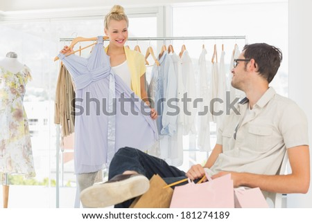 Man sitting with shopping bags while woman selecting a dress in the background