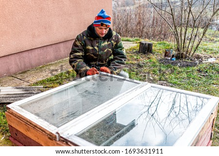 Man sitting working on diy project construction closeup of vegetable winter garden for raised bed cold frame box in Ukraine dacha by farm house ストックフォト ©