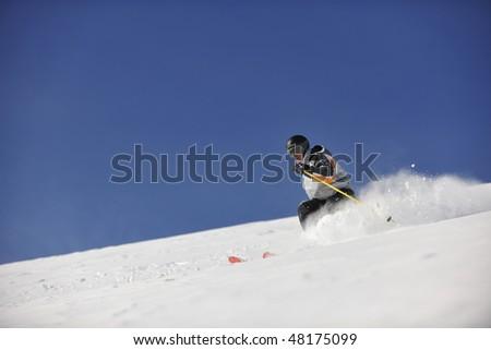 man ski free ride downhill at winter season on beautiful sunny day and powder snow