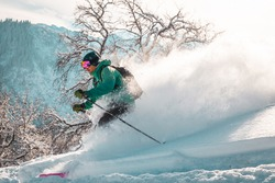 Man skier in green jacket is aggressively free riding in fresh winter powder on the slopes of Trans-Ili Alatau mountains.