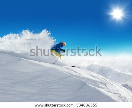 Man skier running downhill on sunny Alps slope #334036355