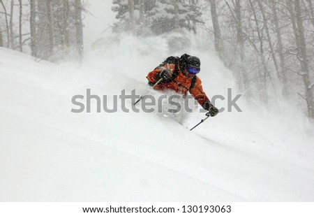 Man skiing deep powder snow during a blizzard in the Utah mountains, USA.