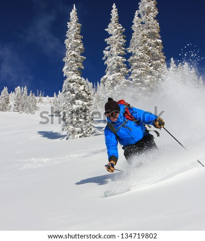 Man skiing powder with frosted trees in the background.