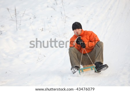 Man sledging down hill, bright and joyful winter scene