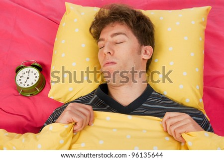 Man sleeping in bed with head on yellow pillow