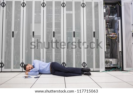 Man sleeping in front of servers in data center