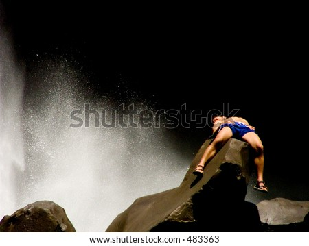 Man sleeping of rock next to waterfall